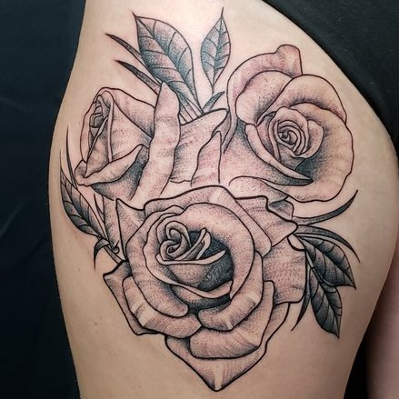 Upper thigh tattoo in black and grey fine lines of three roses.