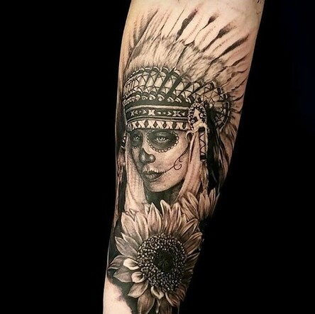 Tattoo of a native american headdress with full skull paint and a sunflower done in black and grey.