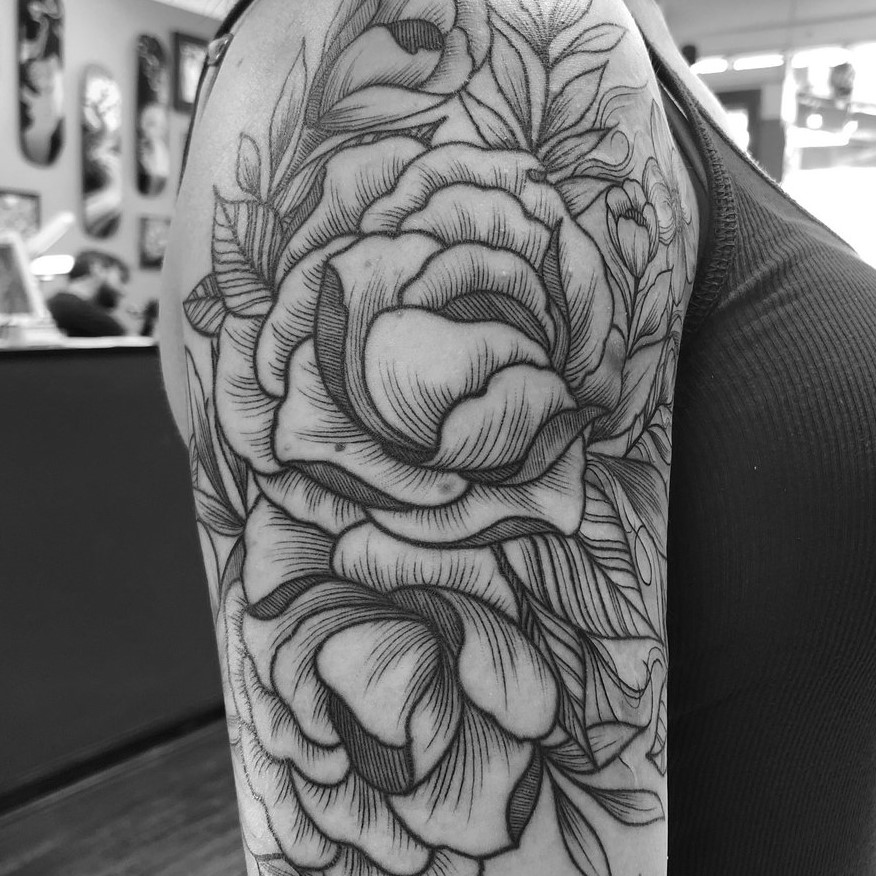 Black and grey fine line flower bicep tattoo of peonies.