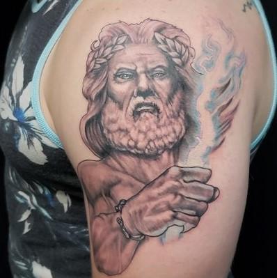 Tattoo of Zeus with a blue lightening bolt on shoulder and bicep done in partial color at Sacred Mandala Studio in Durham, NC.