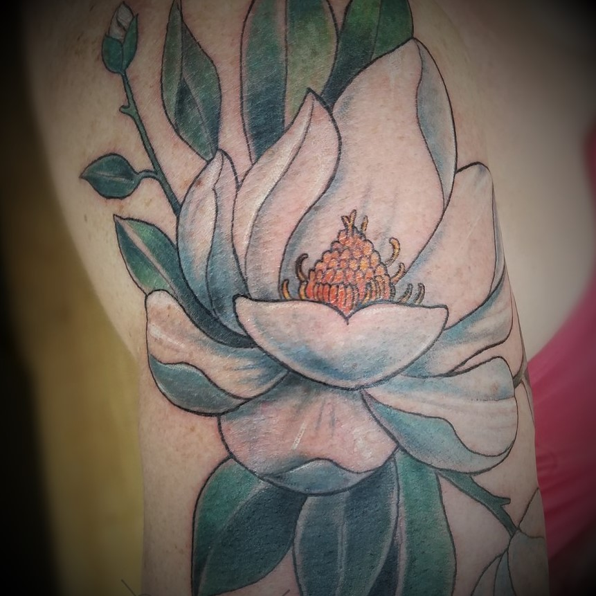 Arm tattoo of a magnolia flower in color. Book your next tattoo at Sacred Mandala Studio in Durham, NC.